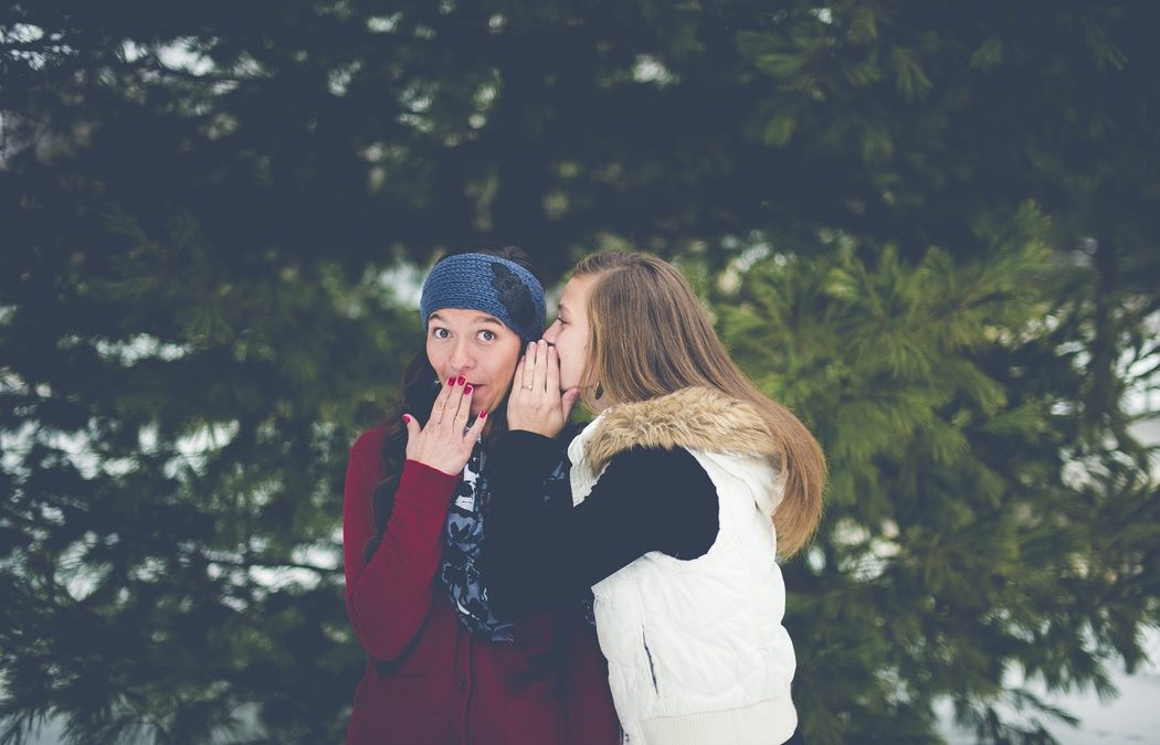 Two women stand gossiping in a field. One is whispering in the ear of the other about someone's freelance business