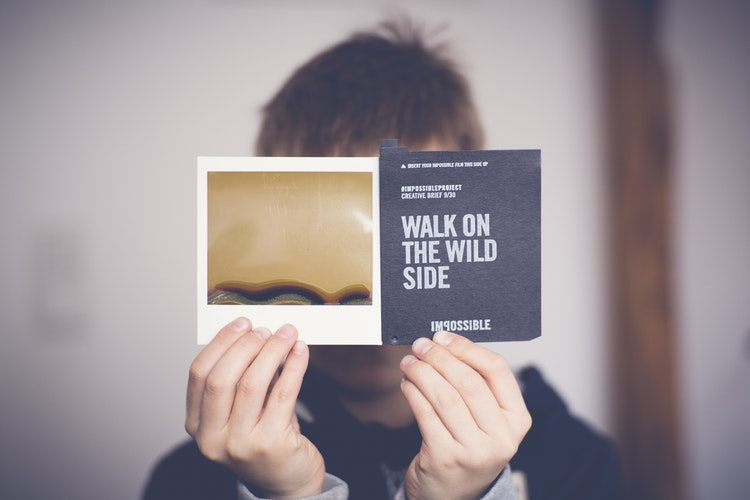 A man holds up a card that reads take a walk on the wild side with impossible underneath. Could this be your call to action for a freelance side hustle or collaboration?