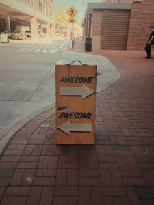 A sign stands in the street pointing arrows left and right to awesome and less awesome. It's used to demonstrate a discussion on th art of feedback.
