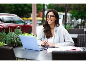 should you go freelance? woman is smiling in front of a laptop in a public place. She has long brown hair and glasses