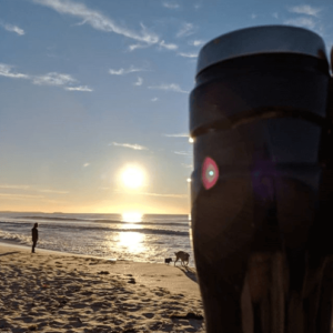shot of a thermos coffee mug mentioned in eco-friendly freelancing article. It is used at a dog beach overlooking sand and waves in Wollongong. There is a man and two dogs in the distance, coffee cup in the foreground