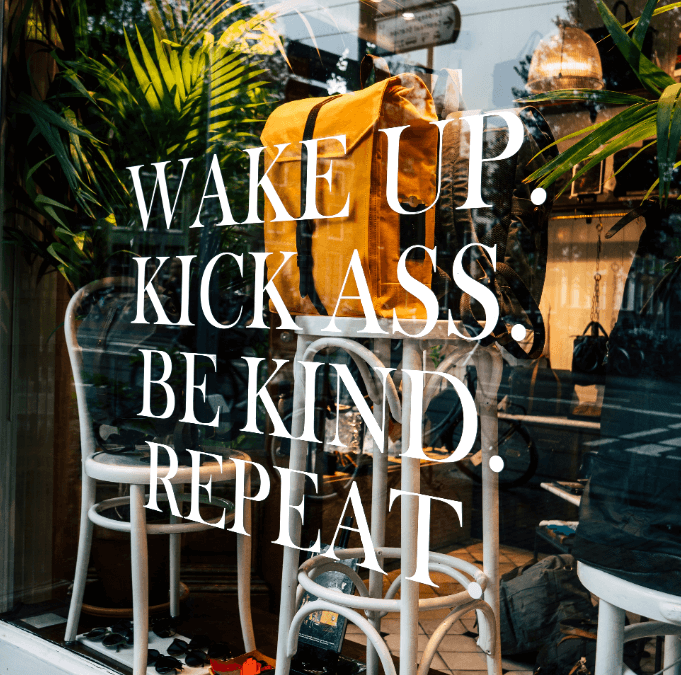 advice for the australian economic downturn includes a sassy cafe window with wake up. kick ass. be kind. repeat. written on it in script with white letters