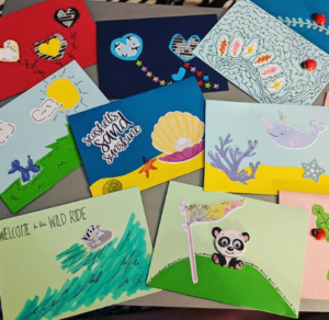 A stack of handmade greeting cards is on a tray table. One of them reads welcome to the wild ride in reference to the title of this blog about COVID-19