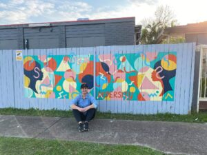 Freelance artists Danielle Said sits in front of a whole fence mural.