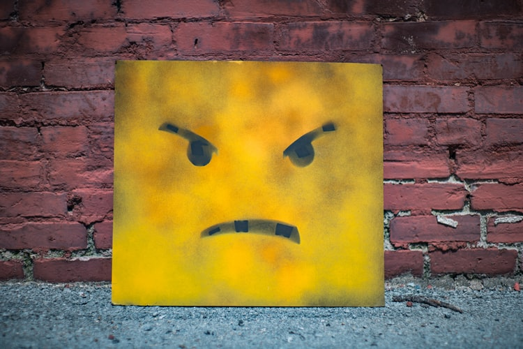 cynicism shows like anger on the face of this yellow sign with downward eyebrows and downturned mouth