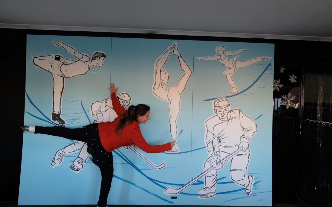 Eva Klusacek. is leaning over her artwork for a local rink. She looks like one of the skaters and she holds her leg high to draw on the wall.