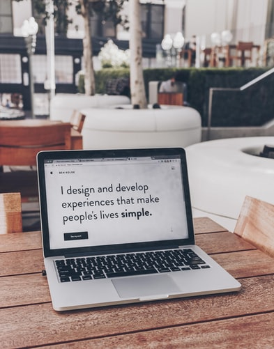 A laptop reads I design and develop experiences that make people's lives simple. It sits on a wooden table in an office.