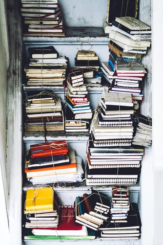 A bunch of journals are bound and stacked in a hall cupboard of a freelance writer or keen journaler.