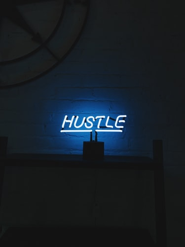 a neon light on a wall reads hustle to demonstrate hustle culture. The room is dark except for the light.