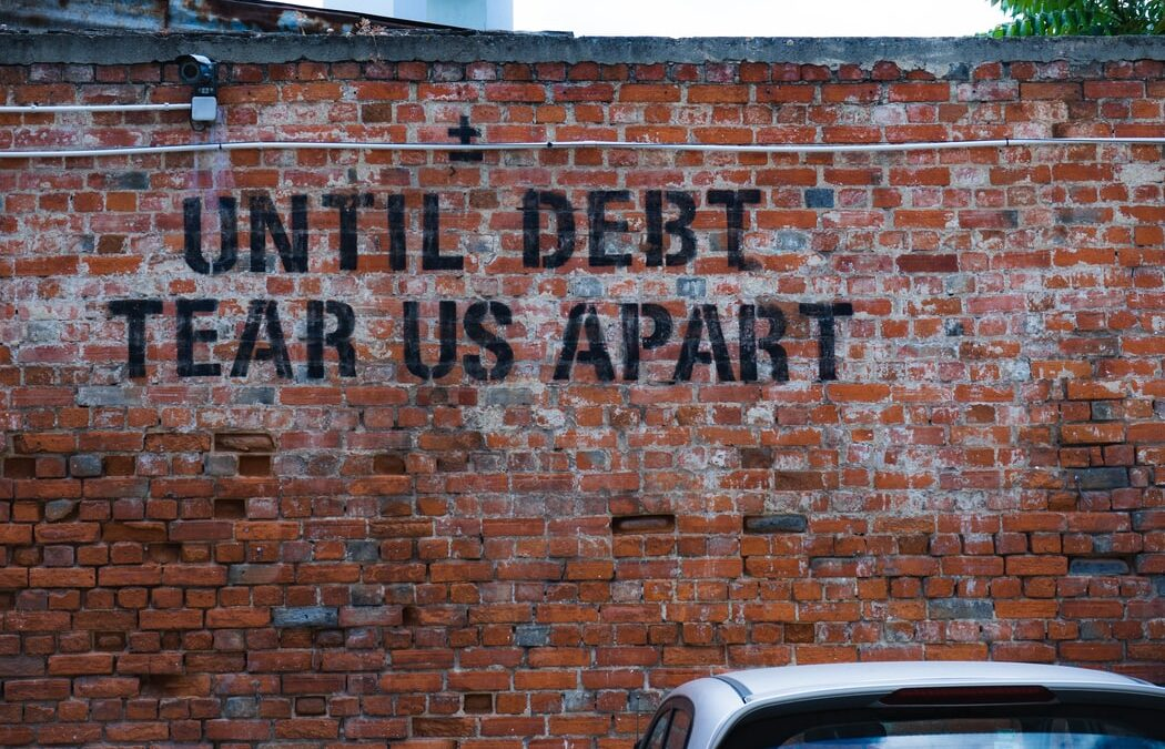 "To highlight the impact of not having effective freelance debt collection strategies, a stencil graffiti on a brick wall reads until debt tear us apart"" there is also the top of a car visible in the right hand bottom corner."