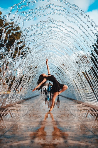A woman stands in the centre of a walk way under an arch made of water. Her body is on tip toes, her head and long dark hair is thrown back. He pose is about building confidence and it's evident she doesn't care what others in the background think. It makes her appealing and beautiful.