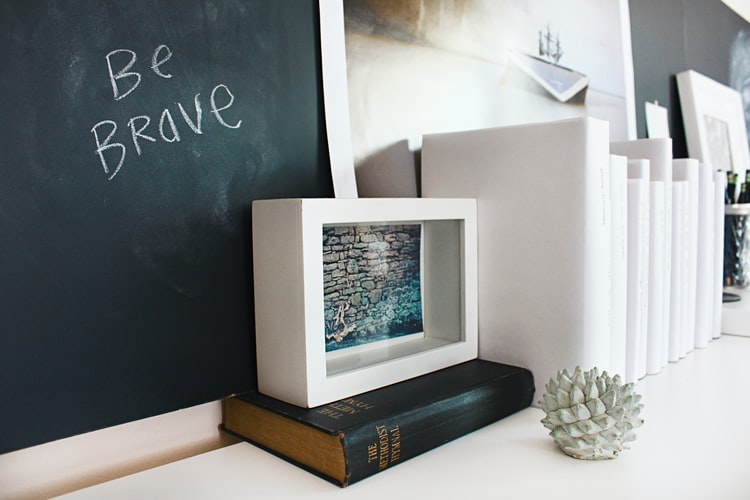a chalkboard says be brave with a white block in front of it with an old book to signify business bravery