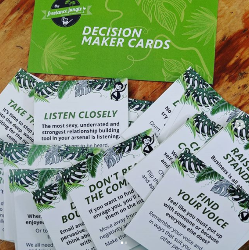 A bunch of freelance jungle decision making cards sit on a table to demonstrate helping making good self-care for the self-employed decisions