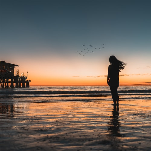 A person with long hair stands in the ocean at sunset a building is off to the side. this moment in the ocean is great freelance self-care