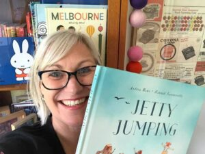 Andrea Rowe holds up her book Jetty Jumping. She is a blonde woman with dark framed glasses smiling at the camera in front of a Melbourne poster