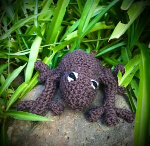 A knitted critter with tentacles and googly eyes sits atop a rock with grass in the background. It was made by freelance maker Lorna Hendry