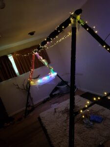 Lights are wrapped around an old triangle shaped swing frame in a bedroom