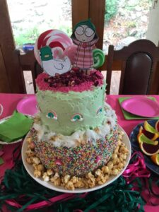 A cake of 8 layers is on a dining room table. On the very top is an oversized headed girl with a duck. It is surrounded by coloured plates