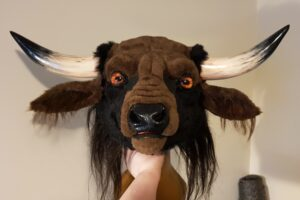 A fluffy headed minotaur looks out at the world, it's amber eyes aflame