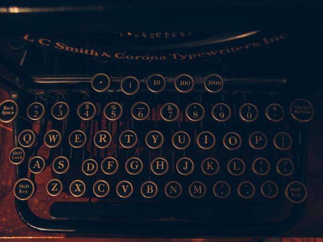 An old fashioned typerwriter is dark and brown with round keys. Freelance fiction writers would only use this if they were dedicated or insane