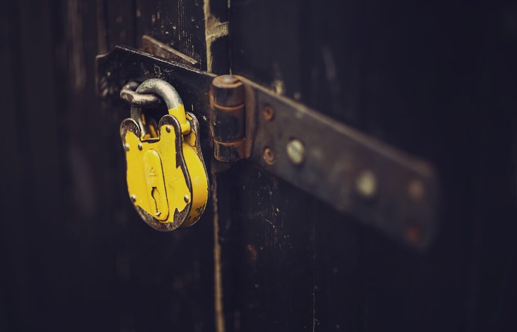 A yellow padlock stands out against a rusted old wall, kind of like these tips on password security
