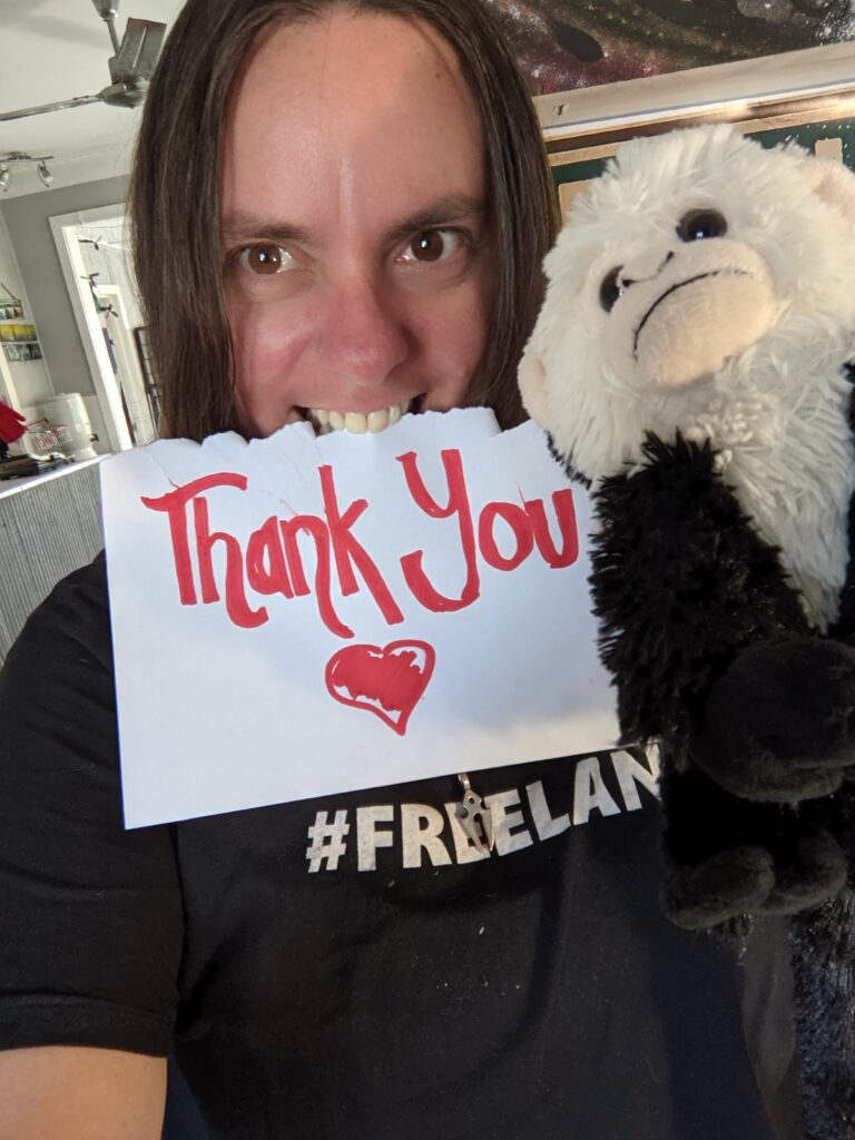 A woman with shoulder length straight brown hair and dark brown eyes has a piece of paper in her mouth and a toy monkey looking like a member of her hip hop crew looking cool and casual at the camera. Her sign reads thank you in red with a heart. Her tee shirt says #freelance