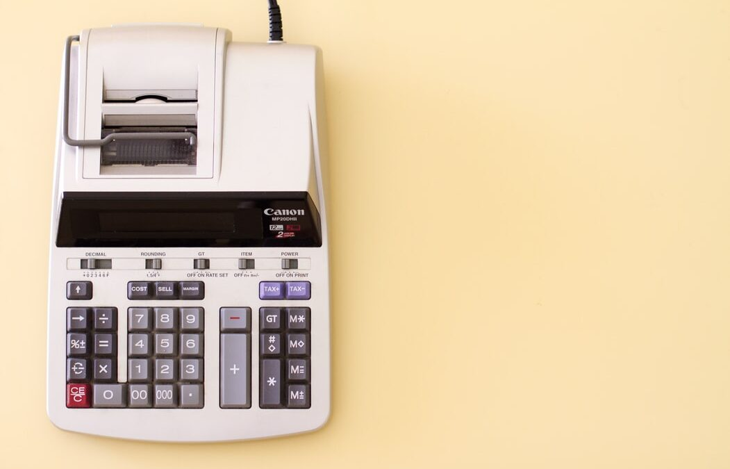 Ten key accounting calculator on yellow desk should be used in conjunction with accounting software freelancers use