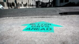 """a spray painted sign reads """"better days ahead"""" on the sidewalk. in this instance, we're referring to better days through freelance fulltime"""