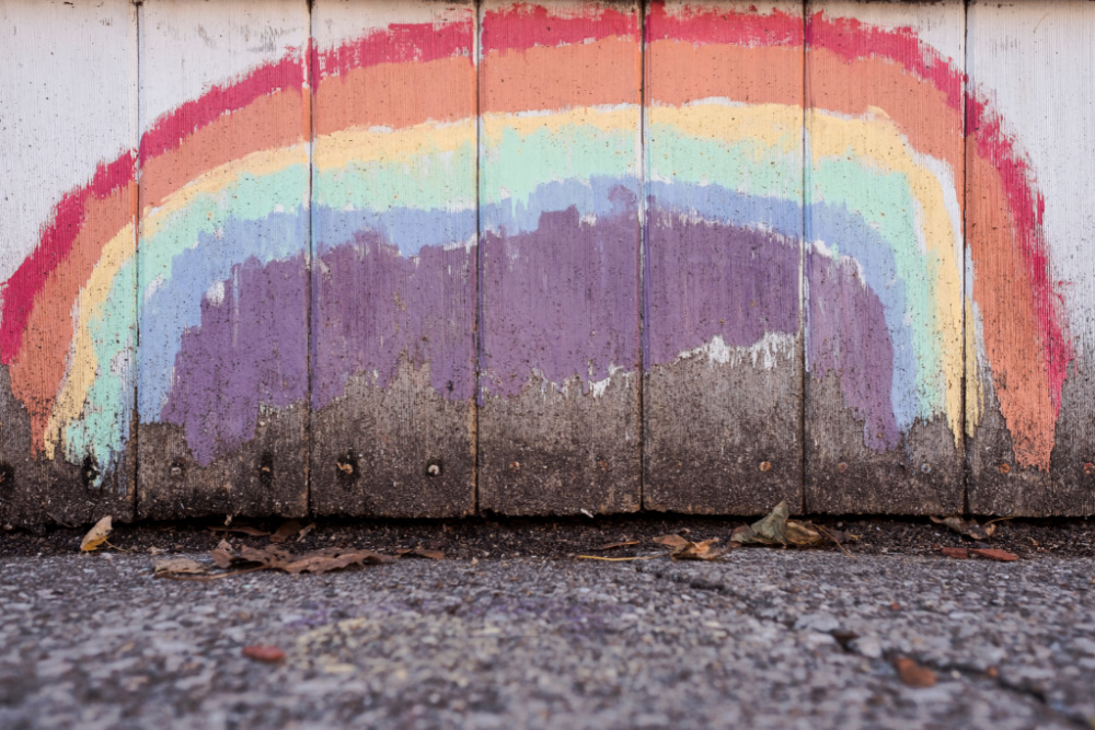 A rough rainbow has been painted on a wall