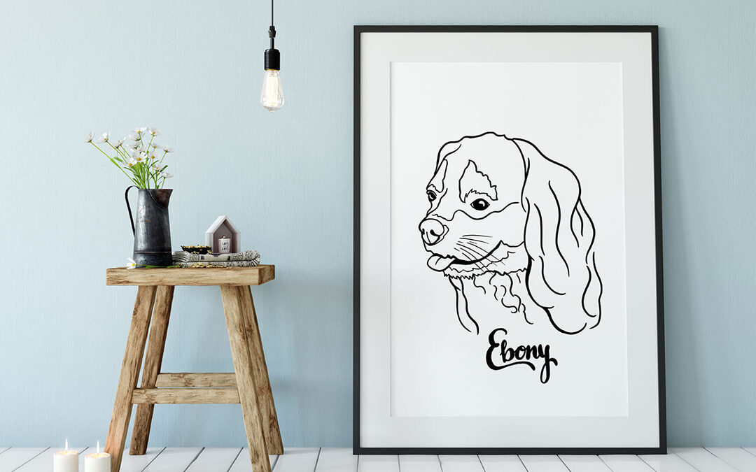 A framed black and white line portrait of a dog with long floppy ears called Ebony is leaning against a blue wall in a room with white floor boards. To the left there are flowers in a black jug on a small coffee table.