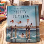 """A children's book """"Jetty Jumping"""". It's cover is an illustration of childrenjoyfully jumping from a jetty into the sea."""