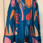 A blue skirt with a pattern of large geometric shapes in contrasting colours. shapes