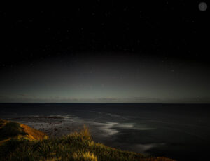A photograph of the night sky and landscape with city light glowing softly in the distance.