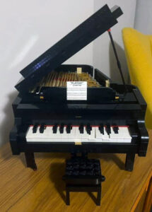 """A model of a grand piano made out of Lego. Tiny sheet music for """"Playday"""" sits on its stand"""