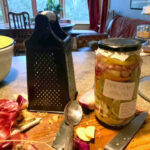 """A jar labelled """"Fire Cider"""" sits on the kitchen bench. There is a grater next to it and a chopping board with red onion skins."""