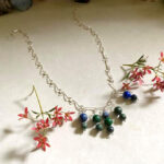 A handmade silver wirework chain featuring five pin pendants made up of round malachite and azurite beads.
