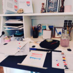An illustrator's desk. On it is an in-progress illustration of a cake, a paint palette, paint brushes and a jar of water and books, etc.