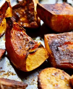 Close up of pieces of roast pumpkin with lots of caramelisation on a tra. It looks delicious and has beenseasoned with sea salt.