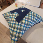 A cushion made out of a blue check or plaid pattern with a large dark blue letter A sewn on to it.