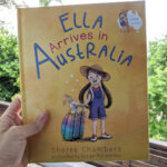"""A children's book """"Ella arrives in Australia"""". It's yellow cover has an illustration of a little girl with ponytails and a hat who holding a multicoloured wheely suitcase."""
