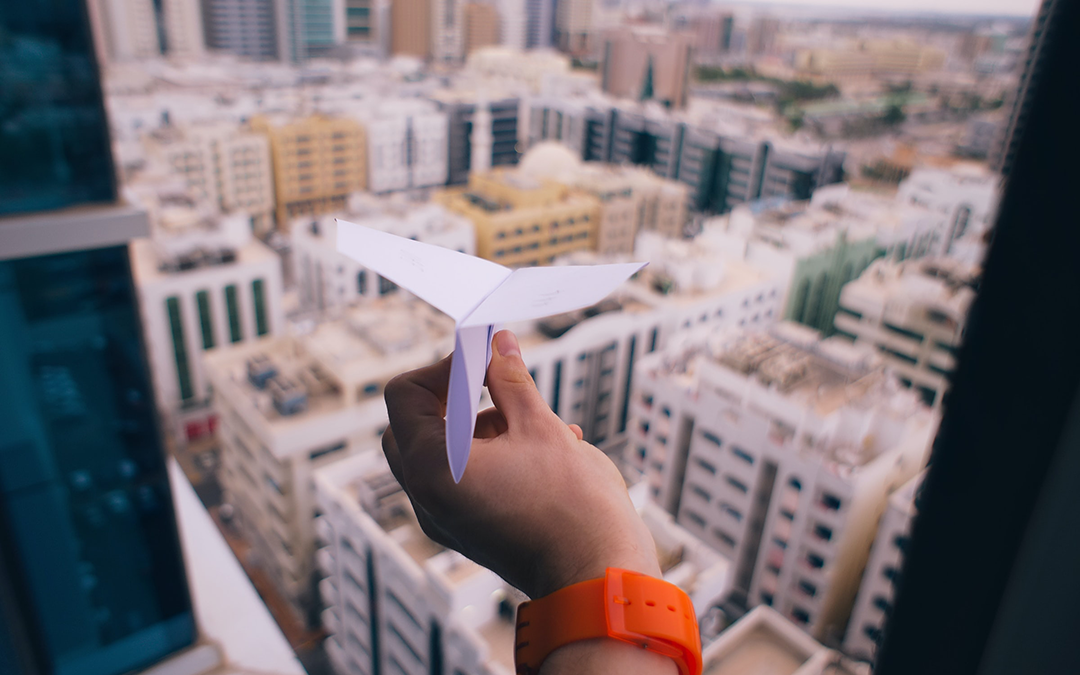 A freelancer's hand holds a paper plane out an open window that overlooks office buildings. The freelancer is procrastinating.