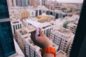 A freelancer's hand holds a paper plane out an open window that overlooks apartment and office buildings. The freelancer is procrastinating.