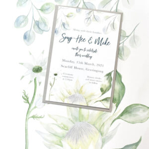 A wedding invitation is shown on a soft floral background. The invitation has a similar background and the wedding details are written in a elegant script.