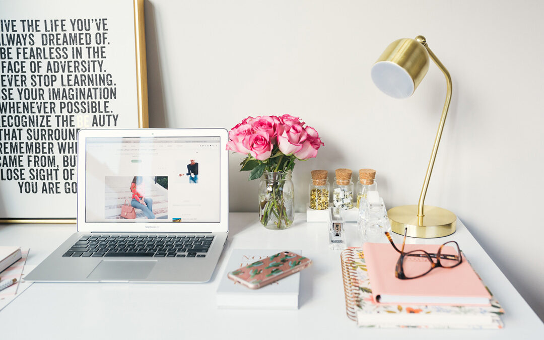 A freelancer's desk with a laptop, lamp, pink roses in a vase, pink notebooks and a motivational image behind the laptop. Photo by Arnel Hasanovic on Unsplash
